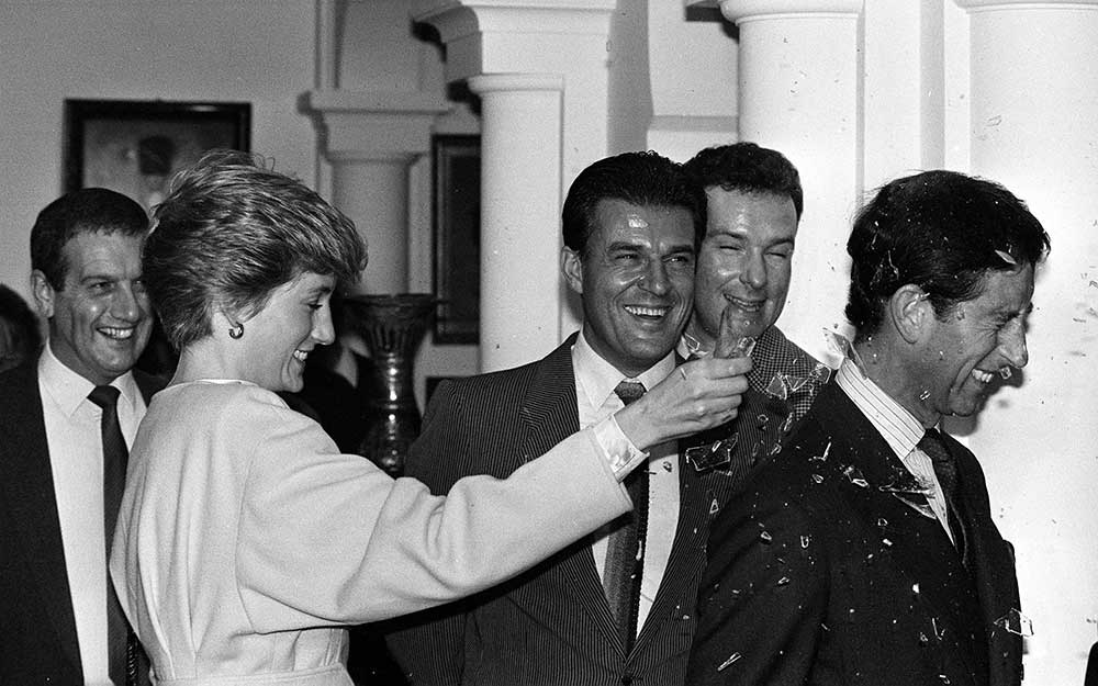 Jeroen-Krabb?-watching-as-Princess-Diana-smashes-a-fake-bottle-over-the-head-of-Prince-Charles-during-a-visit-to-the-set-of-The-Living-Daylights-at-Pinewood-Studios-1986.jpg